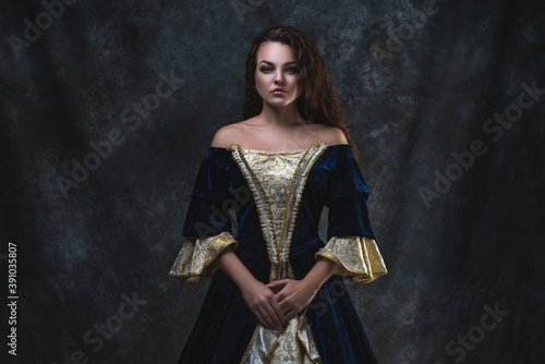 Fototapeta Beautiful woman in renaissance dress on abstract dark background
