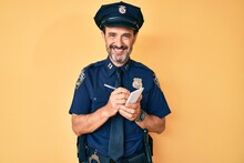 Middle Age Hispanic Man Wearing Police Uniform Writing Traffic Fine Smiling With A Happy And Cool Smile On Face. Showing Teeth.