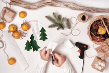 DIY Christmas Home Decor From Natural Materials. Hands Make Garland Of Paper Trees, Twine And Cones