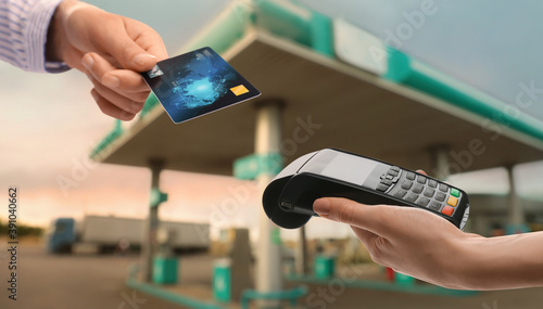 Fotografie, Obraz Woman paying for fuel using credit card via payment terminal at gas station, clo