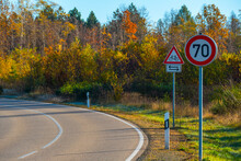 Unused Road With Speed Limit 70 Km/h Signs, In The Background A Beautiful Autumn Forest In Sunlight
