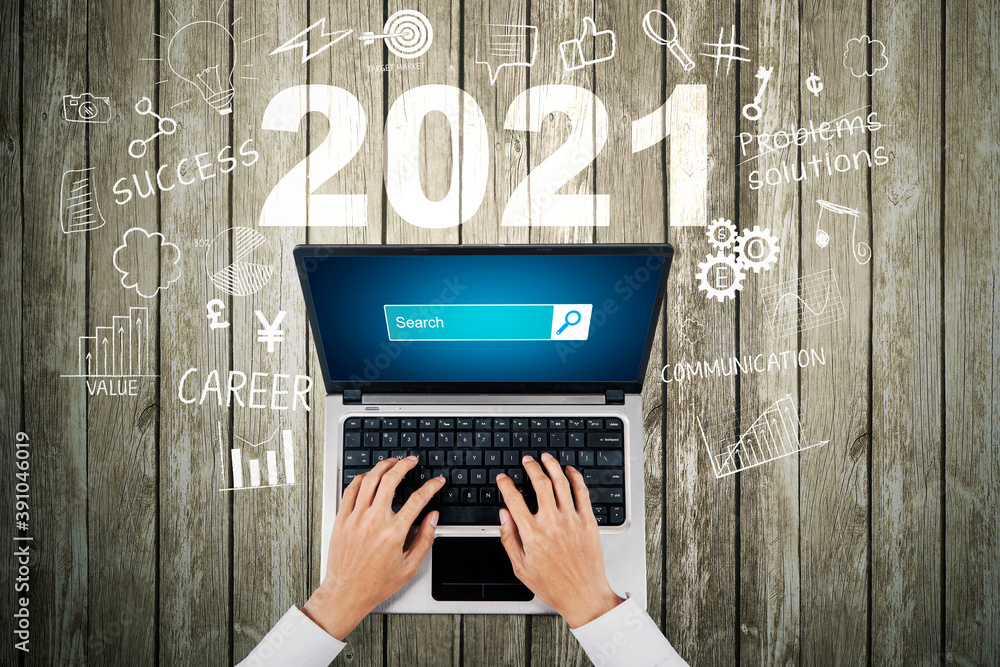 Fototapeta Businessman hands using laptop with 2021 numbers