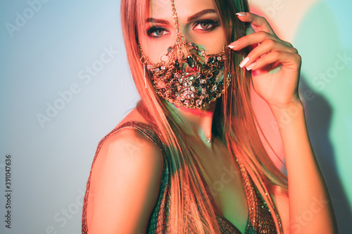 Obraz Pandemic fashion. Neon light portrait. Oriental beauty. Party look. Sensual woman in handmade chain face mask matching gold festive outfit posing in pastel green blue glow copy space background. - fototapety do salonu
