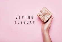 Giving Tuesday. Global Day Of Charitable Giving After Black Friday Shopping Day. Woman Hand Holding Gift Box On Pink Background