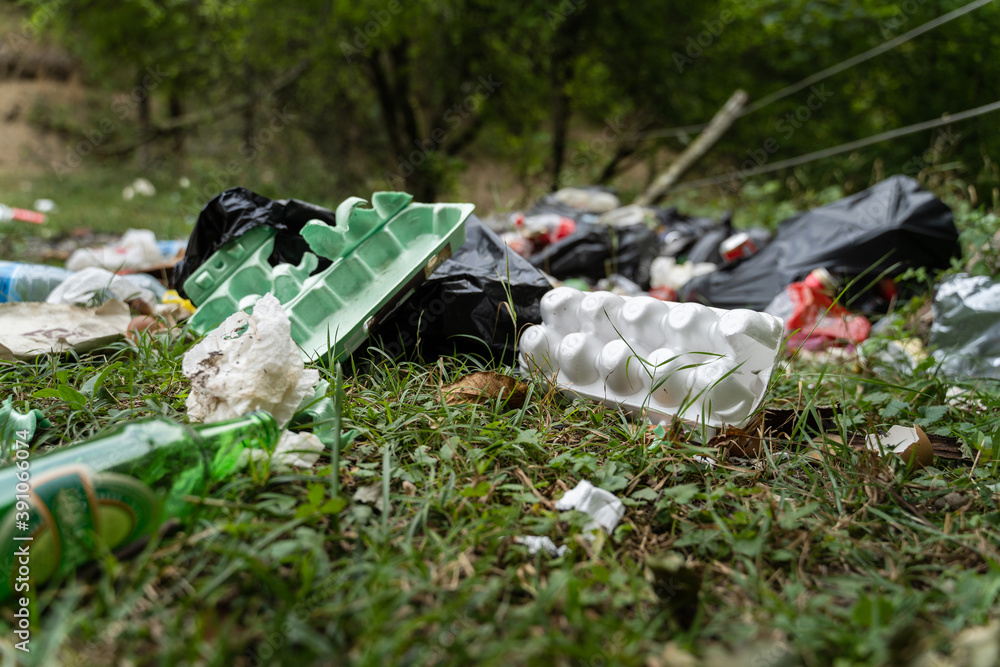 Fototapeta Pollution in nature - garbage thrown on the field covering grass - trash in the countryside on illegal dump