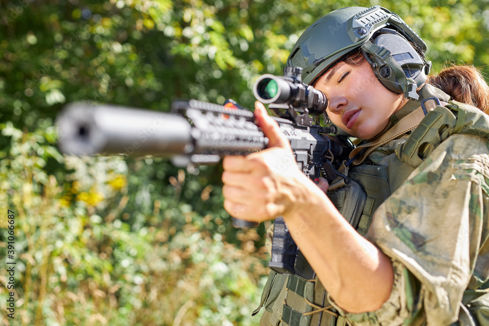 Fototapeta attractive brave military woman with a gun in forest, survival in wild forest, caucasian female in green suit camouflage suit with rifle or weapon
