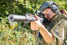 Attractive Brave Military Woman With A Gun In Forest, Survival In Wild Forest, Caucasian Female In Green Suit Camouflage Suit With Rifle Or Weapon