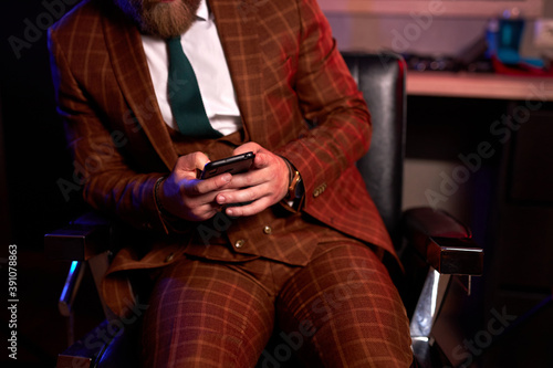 Fotografiet cropped male in elegant suit sitting with mobile phone, chatting with someone