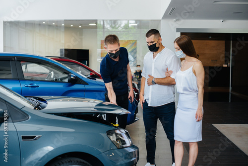 Young couple in masks selects a new vehicle and consult with a representative of the dealership in the period of the pandemic Billede på lærred