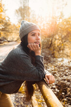 Portrait Of A Very Beautiful Woman In The Autumn Season Leaning On The Fence Of A Very Light Forest Road With The Leaves Of The Orange And Yellow Trees. The Woman Is Wearing Warm Clothes And A Hat