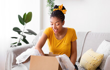 Happy Black Woman Unpacking Parcel After Online Shopping