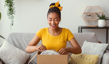 Happy Black Woman Unpacking Box After Online Shopping