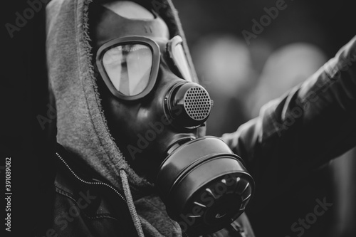 Shallow depth of field (selective focus) image with a protestor wearing a hoodie and a military gas mask Canvas-taulu