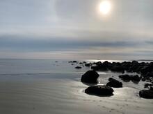 El Sol Brilla Sobre El Mar Rodeado De Una Leve   Bruma,  Las Rocas Contrastan Con Un Negro Intenso