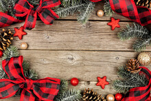 Christmas Frame Of Ornaments, Branches And Buffalo Plaid Check Ribbon. Above View On A Rustic Wood Background.