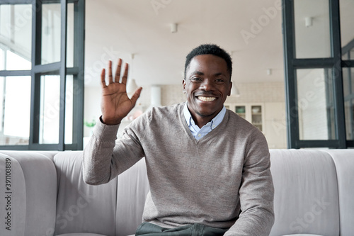 Happy african young man online teacher, coach, distance worker waving hand looking at camera or web cam video conference calling in virtual webcam chat meeting by remote video call Fotobehang