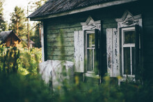 The Facade Of An Old Wooden Summerhouse In The Countryside, In The Shadow Of The Garden With Two Windows And Open Shutters, And Flaking Paint, A Slate On A Triangular Roof, Shallow Depth Of Field