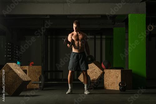 Young bodybuilder training dumbbell alternate biceps curl in home gym Billede på lærred