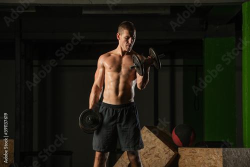 Close up dark portrait of a shirtless young man exercising dumbbell alternate bi Fototapet