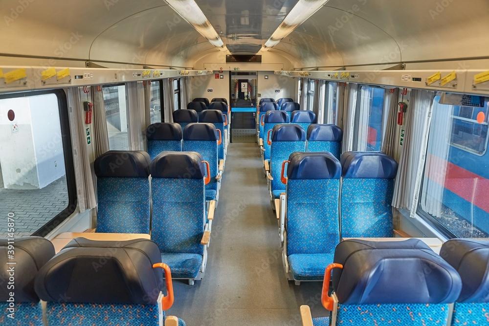 Fototapeta Interior of a passenger train with empty seats, no people during quarantine lockdowns