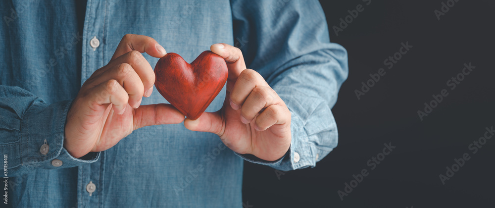 Fototapeta Male hands holding red heart, world mental health day and world heart day, Life and health insurance, concept of love.