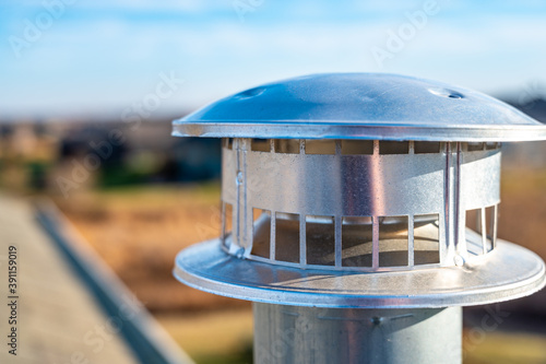 Slika na platnu side view of a Galvanized metal chimney exhaust on  asphalt roof with a rain cap