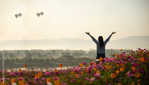 Slika na platnu Asian woman relax and freedom in beautiful blooming cosmos flower garden