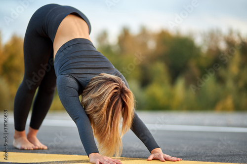 Obraz slim young woman do dog pose, practice yoga on fresh air outdoors, healthy lifestyle, stretching concept - fototapety do salonu