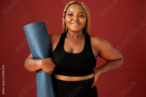 Obraz portrait of beautiful chubby african woman going to do sport exercises alone, hold blue mat in hands, posing at camera, wearing black top and leggins - fototapety do salonu