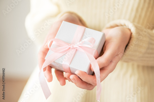 Obraz A woman in a sweater gives a gift in a white holiday packaging box with a pink ribbon. Winter festive cozy life style. Romantic present in female hands for christmas, new year - fototapety do salonu