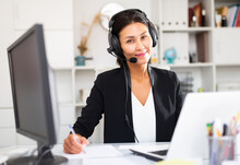 Young Asian Woman Call Centre Operator With Headphones During Working In Modern Office