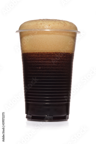 Photo Black stout dark beer in a plastic disposable cup isolated on white