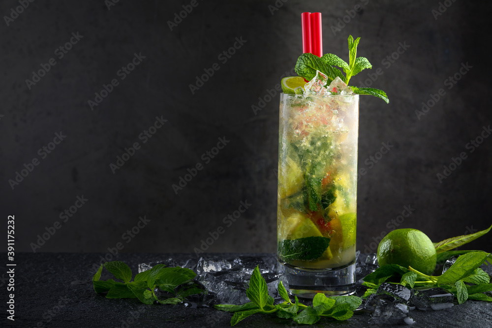 Fototapeta Lime mojito in transparent glass on dark background. Around - pieces of fresh lime, ice and mint. The concept of summer citrus refreshing drinks, cocktails, lemonade
