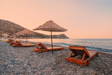 Sunbeds And Sun Umbrellas Await Vacationers On The Shingle Beach At Ovabuku Beach On The Datca Peninsula In Turkey. The Photo Was Taken In The Early Morning At Sunrise