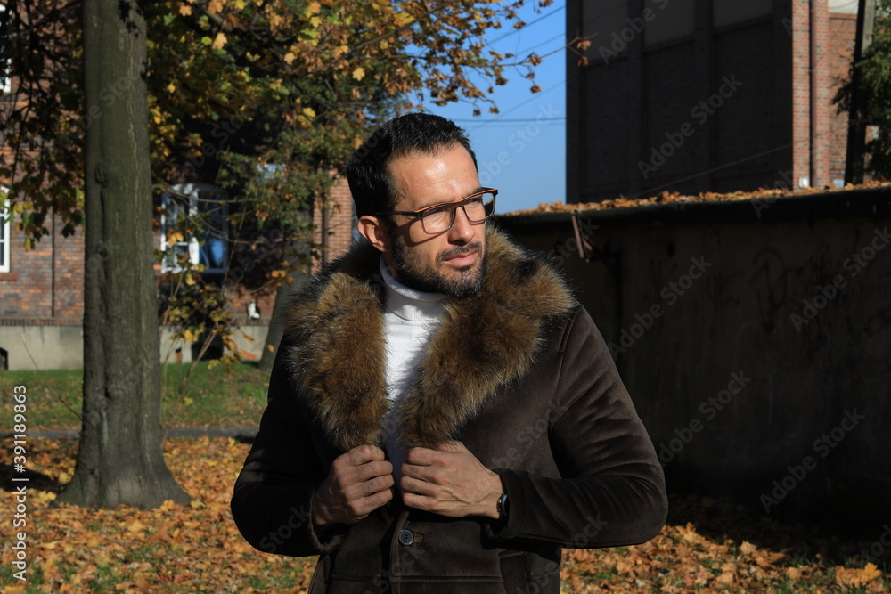 Fototapeta Przystojny mężczyzna w okularach i płaszczu z futerkiem.