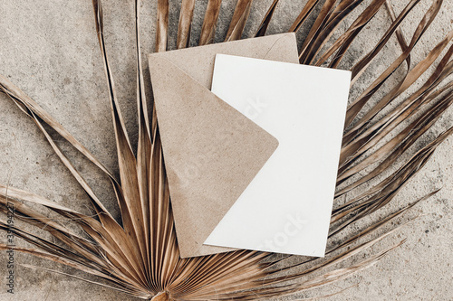 Tropical stationery still life. Closeup of blank card mock-up and craft envelope. Dry palm leaf on grunge beige concrete background. Summer vacation concept. Moody boho design. Flat lay, top view.
