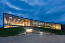 Modern University Buildings, Glass Facade Lit Up At Night, On A Curved Ground Surface