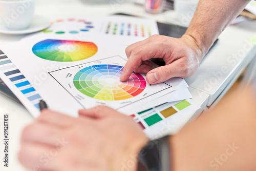 Grafikdesigner zeigt auf die Farbpalette