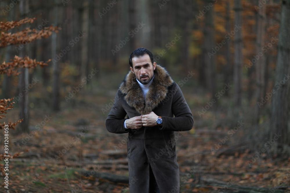 Fototapeta Przystojny mężczyzna w brązowym  płaszczu z futerkiem.