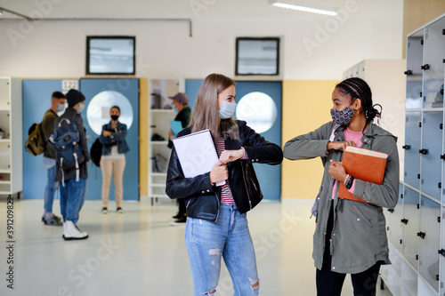 Fotomural Young students friends greeting back at college or university, coronavirus concept