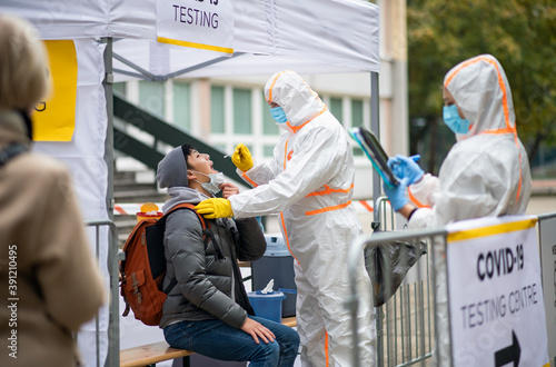 Obraz na plátně Young man in covid-19 testing center outdoors on street, coronavirus and taking swab concept