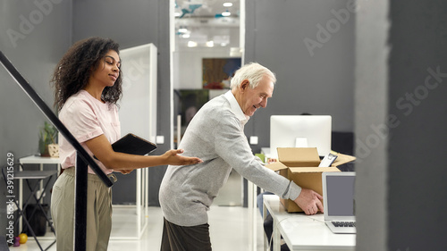 Fototapeta Friendly female company executive supporting, welcoming new employee aged man, s