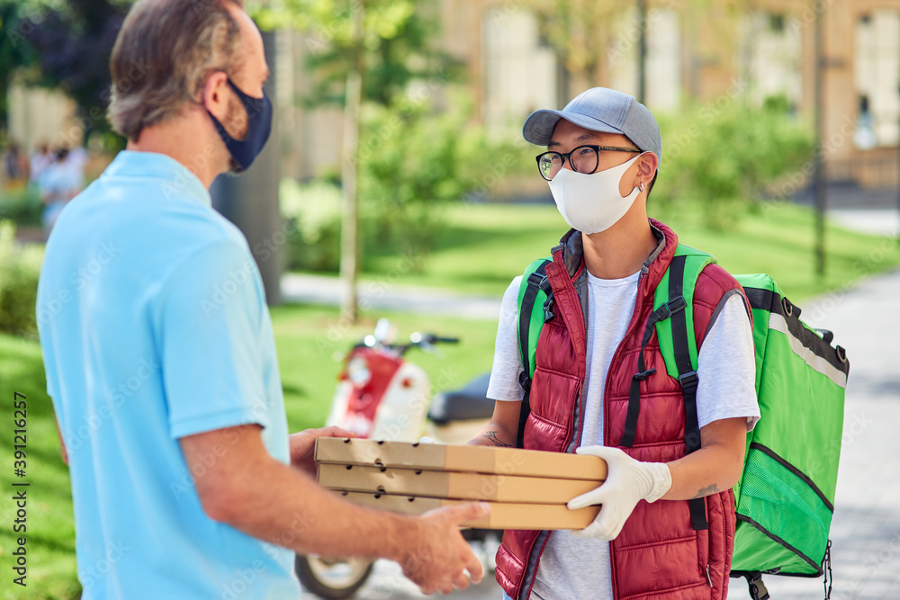 Fototapeta Young asian courier wearing face protective mask and gloves giving boxes with pizza to customer while standing on a sunny street. Food delivery during coronavirus pandemic