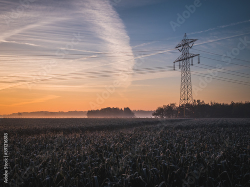 Fotografia Electricity pylon during sunrise in autumn