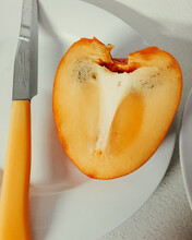 Slice Of Persimmon On White Pl...