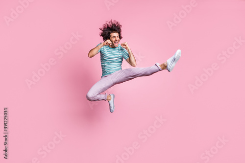 Fotografia Full length photo of handsome young guy dressed casual clothes jumping fighting