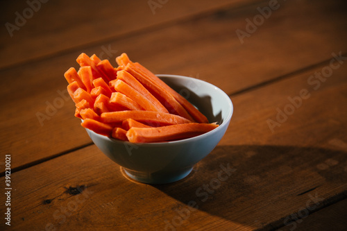 Tela Carrot pieces in a white plate on wooden table. Healthy snack