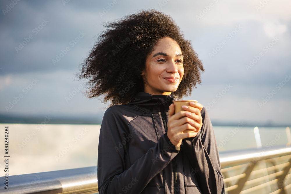 Fototapeta Cheerful beautiful sportswoman smiling and drinking coffee