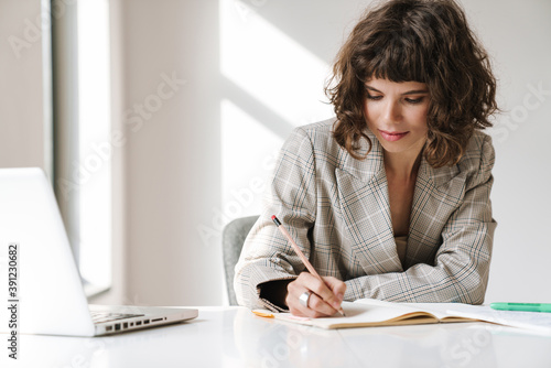 Photo Young beautiful girl making notes while working with laptop in office