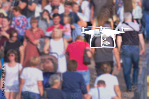 An aerial drone with a camera flies and shoots video over a crowd of people Fototapeta